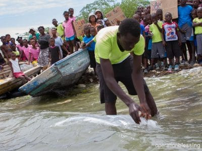 Haitian students stand with their signs to celebrate Earth Day as a thousand tilapia fingerlings are released into the lake.