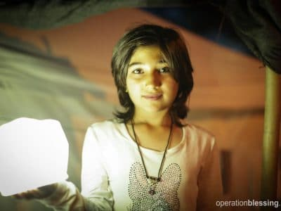 Basha stands with a solar lantern in her tent in Greece